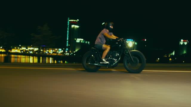 młody biały rowerzysta jazda opracowany specjalnie cafe racer motocykl w mieście w nocy, widok z boku stabilne materiał filmowy - ludzka osada filmów i materiałów b-roll
