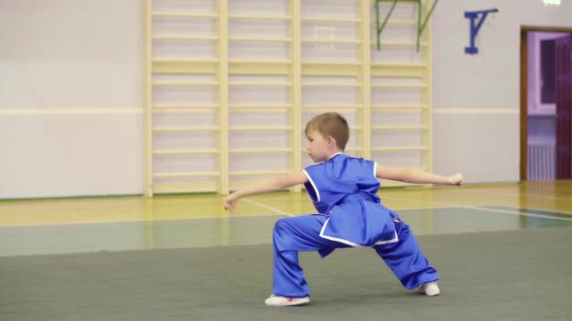 Young caucasian boy in national Chinese dress is practicing Kung Fu wushu tai chi form Nanquan southern fist exercises