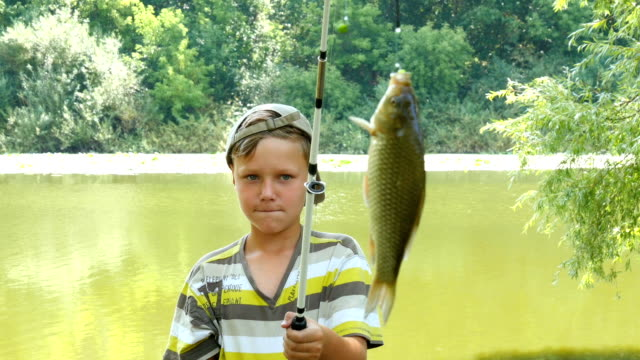 Young Caucasian Boy With Fishing Pole And Fish A little boy caught a fish on a fishing rod catching stock videos & royalty-free footage