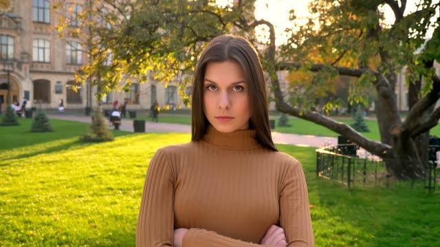 la giovane ragazza bruna caucasica guarda con orgoglio e rabbia sullo sfondo del parco verde. - distrarre lo sguardo video stock e b–roll