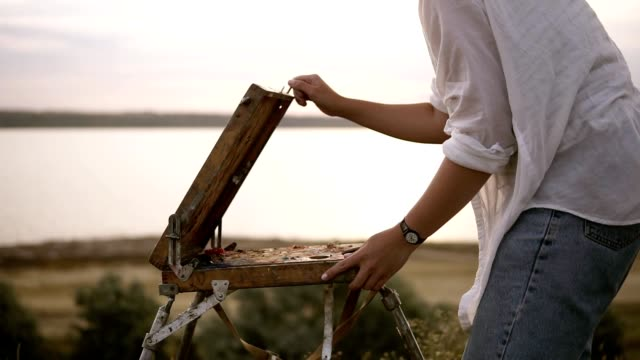 young caucasian brunette ispreparing her easelfor work outdoors. clear meadow with the blurred view of lake on the background - cavalletto attrezzatura per arti e mestieri video stock e b–roll