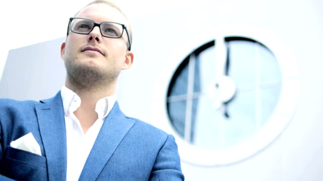 Young Caucasian Businessman in Business Wear. Standing against a Huge Clock and Urban Skyscraper Background. video