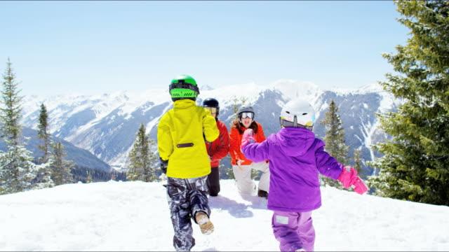 Young Caucasian children parents enjoying winter snow vacation video