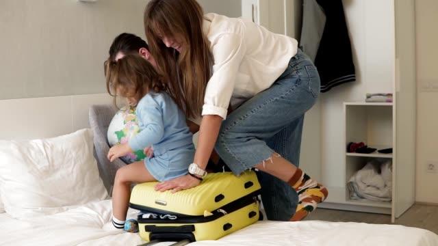 Junge kaukasische Paar versucht, Koffer voller Kleidung zu zip. Eltern schließen Koffer und bitten ihre kleine Tochter, darauf zu sitzen und zusammenzuschieben. Verpackung, Familienreisekonzept – Video