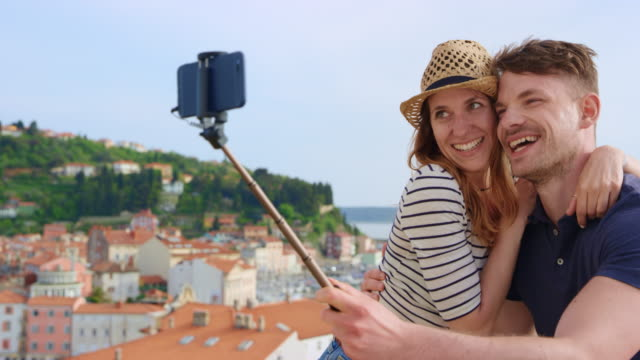 Young Caucasian couple using a selfie stick and taking selfies on a walkway above a coastal town