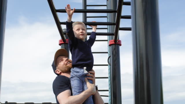 stockvideo's en b-roll-footage met jonge kaukasische papa helpt peuter bewegen over monkey bar - ladder
