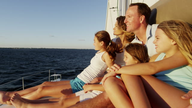 young caucasian family outdoors enjoying sunset yacht vacation - financial planning stock videos & royalty-free footage