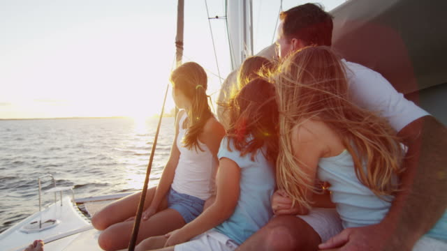 young caucasian family outdoors enjoying sunset yacht vacation - vacanze video stock e b–roll