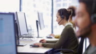 istock Young Caucasian female call center agent talking with a customer at her workstation 1163715776