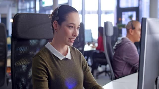 vidéos et rushes de ds young caucasian femme agent de centre d'appels fournissant le service à la clientèle à son poste de travail - relation client