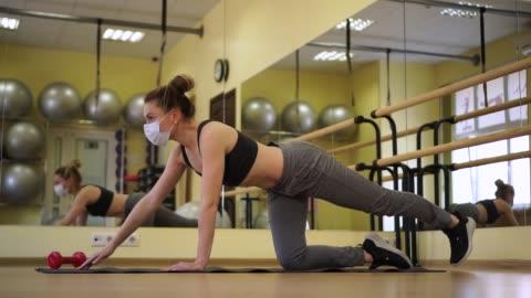 giovane allenatore di fitness femminile caucasica in abbigliamento sportivo fare esercizio pilates su tappetino nero in palestra vuota in maschera protettiva medica. quarantena. fitness a casa - allenamento video stock e b–roll