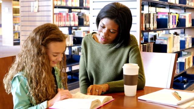 junge kaukasischen weibliche home school grundschüler wird tutored von afroamerikanischen weibliche lehrer in der bibliothek - nachhilfelehrer stock-videos und b-roll-filmmaterial