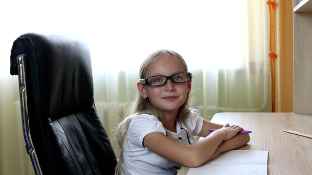young caucasian girl in glasses sitting on chair by table. indoors close up view on pretty girl in glasses. white caucasian girl wrote down by pen on paper. back to school concept close up shot. - school supplies stock videos and b-roll footage