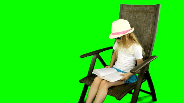 Young caucasian girl in white t-shirt and hat sitting on chair and reading book carefully. video