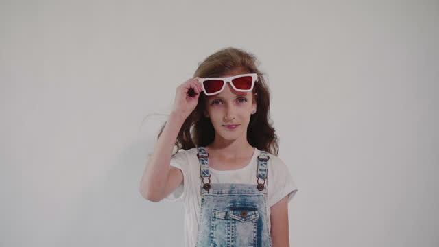 Young caucasian girl lifts her glasses with red lenses and looks at the camera.