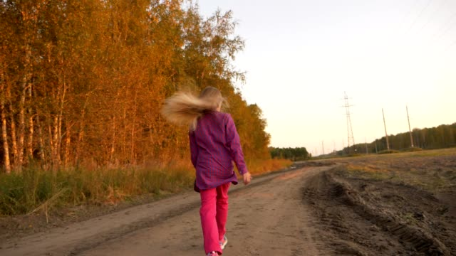 Young caucasian girl running jumping by country road. White blonde long hair girl jumping outdoors. video