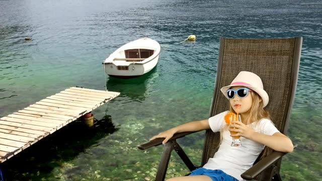 unga kaukasiska flicka sitter på fåtölj och dricka apelsinjuice cocktail genom sugrör. allvarlig ung flicka tittar. ensam båt swaing på vågorna i havet. träbrygga på grönt vatten havet. - solar panel bildbanksvideor och videomaterial från bakom kulisserna