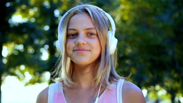 Jovem caucasiano com fones de ouvido ao ar livre em dia ensolarado de verão. - vídeo