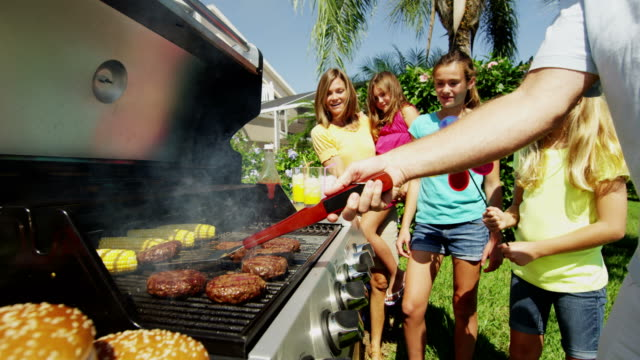 Young Caucasian girls parents using outdoor barbecue grill video