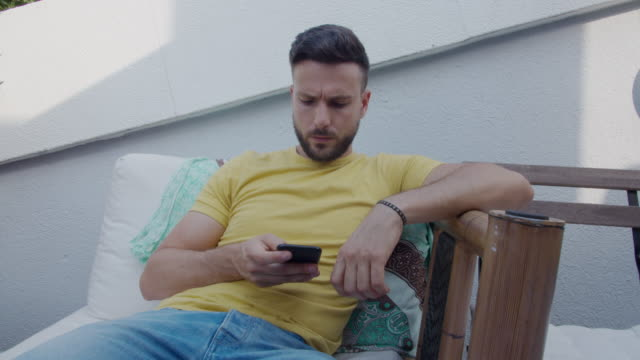 A young caucasian handsome sitting man with a yellow t-shirt and blue jeans texting with the cell phone A young caucasian handsome man sitting outdoors and writing on the mobile phone. He's wearing a yellow t-shirt and blue jeans. one man only stock videos & royalty-free footage