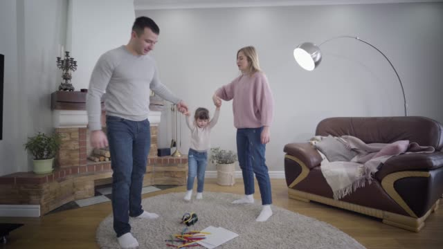 Young Caucasian husband and wife holding daughter's hands and raising child up. Playful positive family enjoying time together indoors. Unity, lifestyle, happiness.