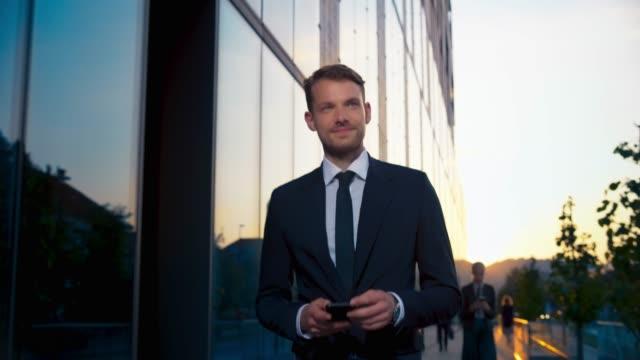 vidéos et rushes de ts jeune homme caucasien mâle d'affaires tapant sur son smartphone tout en marchant le long du bâtiment d'affaires moderne - costume habillé