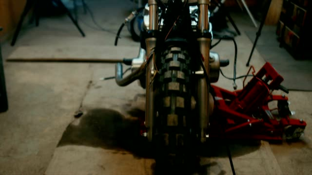 Young Caucasian male mechanic assembling a custom cafe racer motorcycle in a garage video