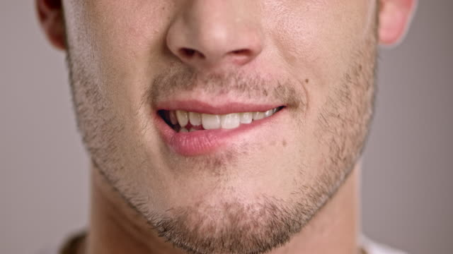 Young Caucasian man biting his lip Close up shot of a young Caucasian man biting his lip. human lips stock videos & royalty-free footage