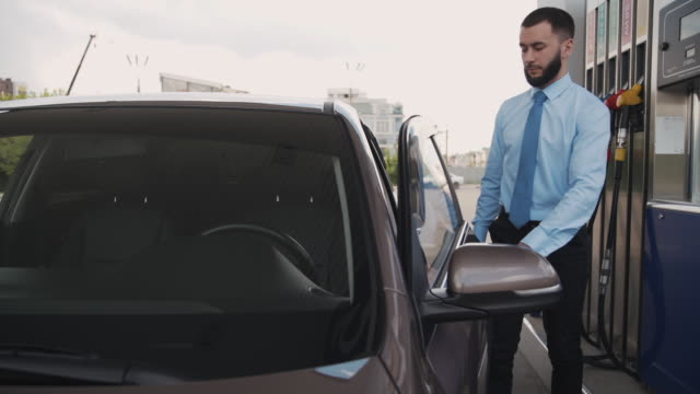 Young caucasian man getting into car after refueling at gas station Young caucasian man getting into car after refueling at gas station. Front of confident bearded businessman opening door of black auto before driving, holding smartphone in hand. Guy wearing classic clothes. button down shirt stock videos & royalty-free footage