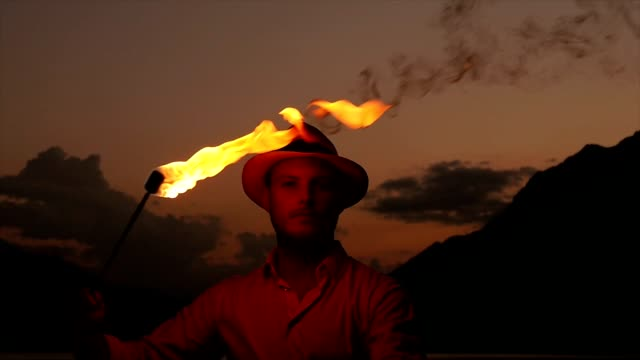 Young Caucasian Man Playing with a Flaming Torch. Fire-Eater, Fire-Breather Using Flames at Night. video