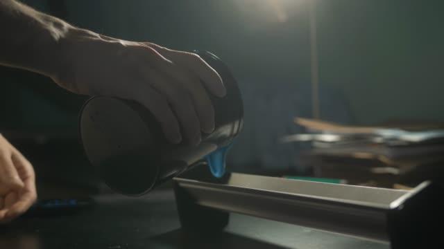 vídeos de stock, filmes e b-roll de homem caucasiano novo que derrama o recipiente com cor azul na oficina no estúdio industrial da cópia. cópia do artesão no serigrafia da t camisa - camiseta preta