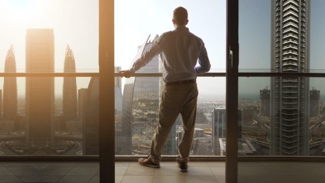 junger kaukasischer mann steht auf balkon mit blick auf moderne stadt mit wolkenkratzern - hoch position stock-videos und b-roll-filmmaterial