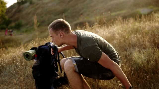 young caucasian man, traveller taking off his backpack on the ground and sits down on the fry grass to take a rest during the hiking. drinking water from the plastic bottle - viaggiare zaino in spalla video stock e b–roll