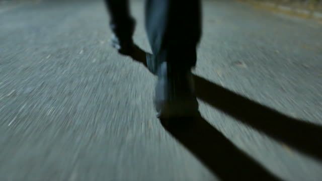 Young Caucasian Man Walking in the Park at Night. Taking a Walk in Casual Clothes. Dark Scenery with Large Shadows.