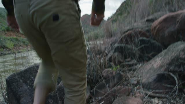 en ung kaukasisk man klädd i en baklänges baseball cap och sandaler vandringar genom brush vid kanten av colorado floden i västra colorado - byxor bildbanksvideor och videomaterial från bakom kulisserna