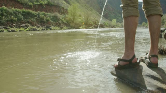 A Young Caucasian Man Wearing Sandals Standing on a Rock Urinates into the Colorado River in Western Colorado on a Sunny Day