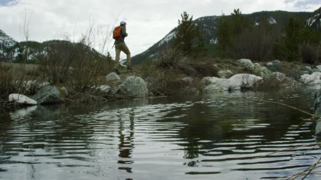 ein junger kaukasischer mann mit einem bart und einem rucksack wandert neben einem snowy mountain stream/lake in den rocky mountains von colorado unter einem overcast sky im winter - bach stock-videos und b-roll-filmmaterial