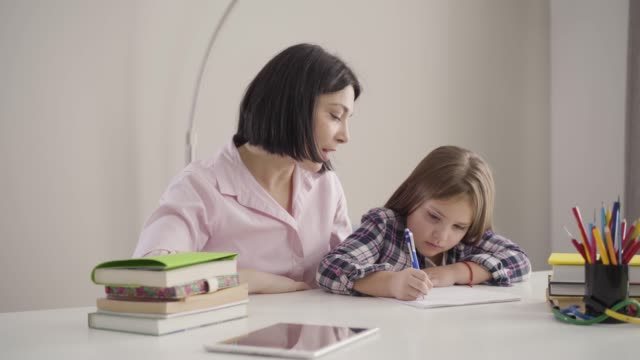 Young Caucasian mother dictating to daughter as pretty brunette girl writing down. Schoolchild doing homework with parent at home. Support, education, intelligence.