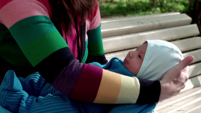 Young Caucasian mother holding her little baby in the Park on a bench. Slow-mo video