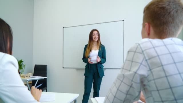 Young Caucasian teacher near whiteboard coaching college students in classroom