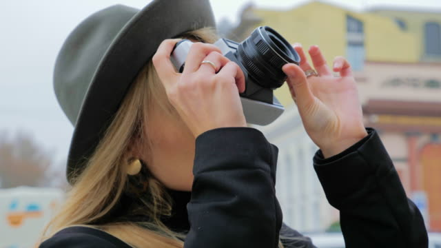 a young caucasian woman, a hipster in a hat takes photos on an old vintage film camera. concept journalist blogger for print edition in work - analogiczny filmów i materiałów b-roll