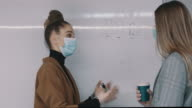 istock Young Caucasian woman and her colleague discussing diagrams shown on the whiteboard in a meeting room wearing mask and gloves during COVID-19 1269989041