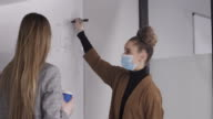 istock Young Caucasian woman and her colleague discussing diagrams shown on the whiteboard in a meeting room wearing mask and gloves during COVID-19 1269993765