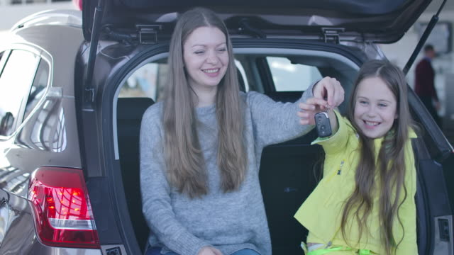 Young Caucasian woman and little cute girl sitting in car trunk and bragging keys. Positive mother and daughter buying new vehicle in dealership. Happy owners posing in showroom. Cinema 4k ProRes HQ.