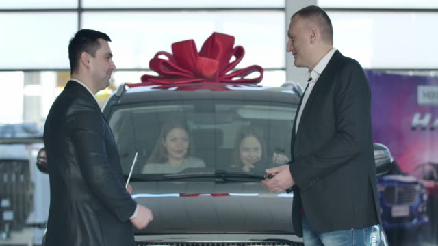 Young Caucasian woman and little girl looking at businessman taking car keys from dealer and shaking hands. Man buying automobile for excited wife and daughter in dealership. Cinema 4k ProRes HQ.