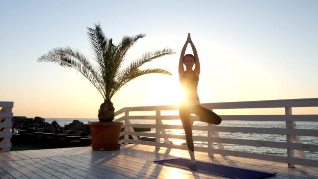 Kaukasische Mädchen tun Yoga Asana in der Natur auf einem hölzernen Balkon über Meer bei Sonnenaufgang. Frau, Praxis am Meer, Entspannung in der Natur. Mädchen in Sportbekleidung. Slow-motion – Video