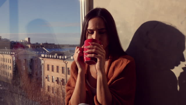 Young Caucasian woman drinking a cup of coffee while sitting on the windowsill with a panorama of city video