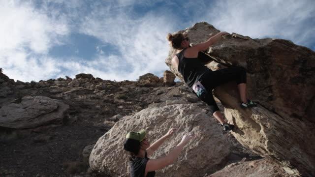 vídeos y material grabado en eventos de stock de joven caucásica libre sube una pared de roca mientras que una mujer joven latina puntos le - escalada en rocas