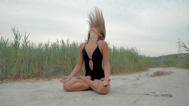 Young caucasian woman in black swimsuit relaxing by practicing yoga on the nature near reeds at summer, close-up of hands, gyan mudra and lotus position. Slow motion video