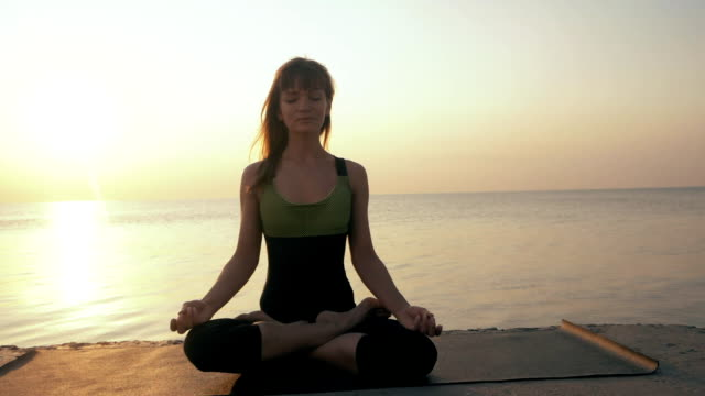 Young caucasian woman in bodysuit relaxing by practicing yoga on the beach near calm sea, close-up of hands, gyan mudra and lotus position. Sunrise background. Slow motion video